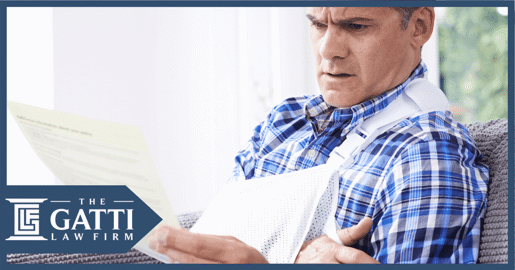 man with injured shoulder looking at insurance papers